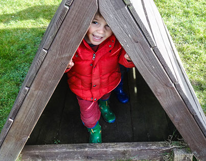 image of a boy in a red coat playing outside on Longscroft home page