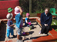 photo of children from Dragonflies playing in a sandpit at Longscroft