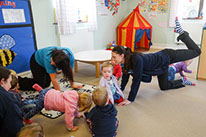 photo showing staff and children in Bumble Bees enjoying baby yoga at Longscroft